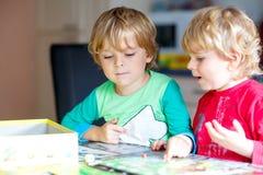 Zwei kleine blonde Kinderjungen, die zusammen zu Hause Brettspiel spielen Lustige Geschwister, die Spaß haben Lizenzfreies Stockbild