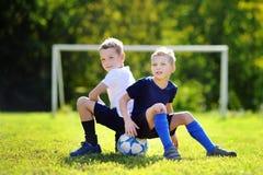 Zwei kleine Brüder, die den Spaß spielt ein Fußballspiel haben Stockfoto