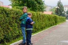 Zwei kleine Brüder, die in den Straßen ihrer Stadt zurück zu Rückseite stehen lizenzfreie stockfotos