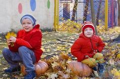 Zwei kleine Brüder, die draußen auf Kürbis im Herbst sitzen Helloween lizenzfreie stockbilder