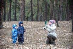 Zwei kleine Brüder, die zusammen mit ihrer Mutter an der Herbstwaldmutter spielen, wird Petard benutzen Stockfotografie