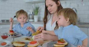Zwei kleine Brüder mit ihrer Mutter in einem Kleid kochen zusammen Burgern einer in den weißen Küche lachen und lächeln stock footage