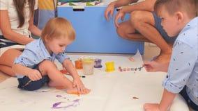Zwei kleine Brüder und ihre Eltern, die mit Aquarellen malen Lizenzfreies Stockbild