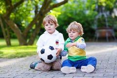 Zwei kleine Fanjungen an der allgemeinen Betrachtung des Fußballspiels lizenzfreies stockbild