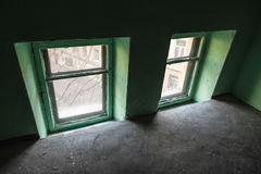 Zwei kleine Fenster in der grünen Wand, städtischer Innenraum Stockfoto