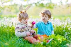 Zwei kleine Freunde in den Osterhasenohren während des Eies jagen Lizenzfreies Stockfoto