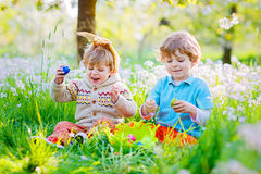 Zwei kleine Freunde in den Osterhasenohren während des Eies jagen Lizenzfreie Stockfotos