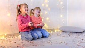 Zwei kleine Freunde, die auf Boden im Raum mit festlichem Dekor sitzen stock video