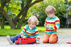 Zwei kleine Freunde, die mit rotem Schulbus spielen Stockbilder