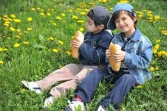 Zwei kleine Freunde, die zusammen essen, Stockbild