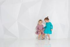 Zwei kleine Freundinnen in den identischen Kleidern von den verschiedenen Farben, die in einem Studio mit weißen Wänden sitzen Lizenzfreie Stockfotos