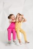Zwei kleine Freundinnen im identischen Overall von den verschiedenen Farben, die auf einem Stuhl in einem Studio mit weißen Wände Lizenzfreie Stockfotos