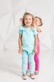 Zwei kleine Freundinnen im identischen Overall von verschiedenen Farben in einem Studio mit weißen Wänden Lizenzfreie Stockbilder