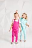 Zwei kleine Freundinnen im identischen Overall von verschiedenen Farben in einem Studio mit weißen Wänden Lizenzfreie Stockfotos