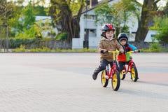 Zwei kleine Geschwister, die Spaß auf Fahrrädern in der Stadt auf Ferien haben Stockfotos