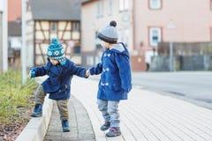 Zwei kleine Geschwisterjungen, die auf die Straße im deutschen Dorf gehen. Stockfotografie