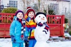 Zwei kleine Geschwisterjungen, die einen Schneemann im Winter machen Lizenzfreie Stockfotografie