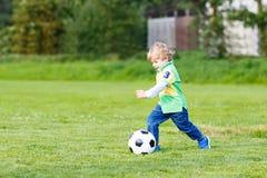 Zwei kleine Geschwisterjungen, die Fußball und Fußball auf Feld spielen Lizenzfreie Stockfotos