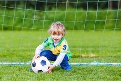 Zwei kleine Geschwisterjungen, die Fußball und Fußball auf Feld spielen Stockfotografie