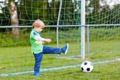 Zwei kleine Geschwisterjungen, die Fußball und Fußball auf Feld spielen Lizenzfreie Stockbilder