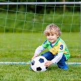 Zwei kleine Geschwisterjungen, die Fußball und Fußball auf Feld spielen Stockbilder