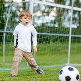 Zwei kleine Geschwisterjungen, die Fußball und Fußball auf Feld spielen Lizenzfreies Stockfoto