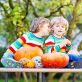 Zwei kleine Geschwisterjungen, die Steckfassung-Olaterne für Halloween in a herstellen Lizenzfreies Stockfoto