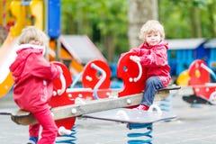 Zwei kleine Geschwisterkinderjungen, die zusammen auf einem Spielplatz, ou spielen Stockfoto