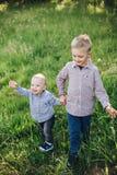 Zwei kleine glückliche Brüder, welche die Jeans und überprüfte Hemden gehen in Park tragen lizenzfreie stockfotografie