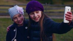 Zwei kleine hübsche Mädchen machen selfie am Handy draußen stock footage