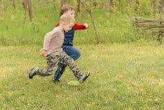 Zwei kleine Jungen, die über ein Feld laufen Stockfotografie