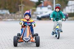 Zwei kleine Jungen, die mit Rennwagen und Fahrrad spielen Stockbild