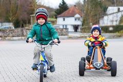 Zwei kleine Jungen, die mit Rennwagen und Fahrrad spielen Lizenzfreie Stockbilder
