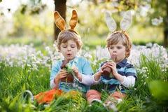 Zwei kleine Jungen, die Osterhasenohren tragen und Schokolade essen Stockbild