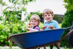 Zwei kleine Jungen, die Spaß in der Schubkarre drückt durch Vater haben Stockfoto