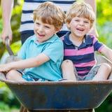 Zwei kleine Jungen, die Spaß in der Schubkarre drückt durch Vater haben Lizenzfreie Stockfotos