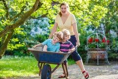 Zwei kleine Jungen, die Spaß in einer Schubkarre drückt durch Mutter haben Lizenzfreies Stockfoto