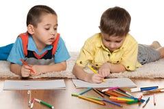 Zwei kleine Jungen, die auf Papier zeichnen Lizenzfreie Stockfotografie