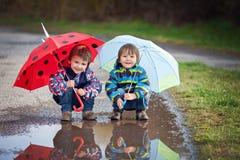 Zwei kleine Jungen mit Regenschirmen Lizenzfreie Stockfotos