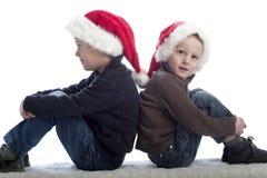 Zwei kleine Jungen mit Weihnachtshüten Stockfotos