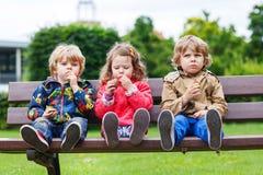 Zwei kleine Jungen und ein Mädchen, die Schokolade essen Stockbild