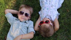 Zwei kleine Kinder in der Sonnenbrille, die auf dem Gras im Park liegt Ansicht von der Oberseite stock footage
