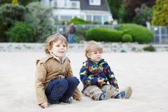 Zwei kleine Kinder, die auf Strand von Fluss Elbe sitzen und t spielen Stockbild