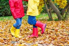 Zwei kleine Kinder, die in den roten und gelben Gummistiefeln im Herbst spielen, parken Lizenzfreies Stockfoto