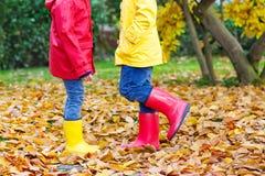 Zwei kleine Kinder, die in den roten und gelben Gummistiefeln im Herbst spielen, parken Stockfotos