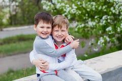 Zwei kleine Kinder, die draußen im Sommer umarmen stockfoto