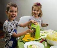 Zwei kleine Kinder, die eine Mahlzeit vorbereiten stockbild