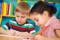 Zwei kleine Kinder, die am Kindergarten zeichnen stockbilder