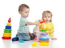 Zwei kleine Kinder, die mit Farbenspielwaren spielen Stockfoto