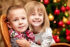 Zwei kleine Kinder im Hintergrund des Weihnachtsbaums Stockfoto